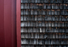 Weathered shingles of an old mill building against a red wood wall Royalty Free Stock Photos