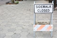 Weathered Sidewalk Closed Sign with Concrete Pavers royalty free stock photo