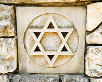 Weathered star of david in rock wall. Ceramic tile in old rock wall with star of David, the religious symbol representing judaism, the jewish faith. Tile is one Royalty Free Stock Image
