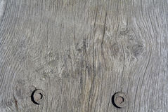 Cracked weathered wood grain details with two bolts. Royalty Free Stock Photography