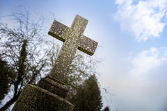 Weathered stone cross or gravestone against the blue sky, memori Royalty Free Stock Image