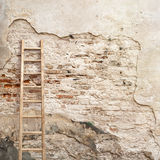 Weathered stucco wall with wooden ladder Royalty Free Stock Image