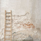 Weathered stucco wall with wooden ladder Stock Photo