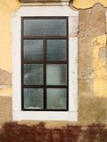 Weathered wall and window. A weathered yellow wall and frosted glass window in Portugal stock photos
