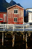 Weathered waterfront property. Red paint peeling off a rustic wooden waterfront house in Lofoten, Norway Stock Photo