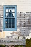 Weathered House and Window. Weathered White House and Blue Window with Peeling Paint Stock Photography