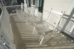 Weathered White Rocking Chairs On A Porch. A row of four used and weathered white painted wooden rocking chairs on an elevated dirty porch at sunrise on a sunny Stock Photo