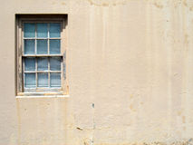 Weathered Window. Double hung window in a stucco building with weathered, peeling paint on the frame and sill Stock Images