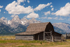 Weathered wood barn below rugged mountain peaks. Abandonded wood barn under blue sky and puffy clouds on Mormon Row in Grand Teton National Park near Jackson Royalty Free Stock Photos