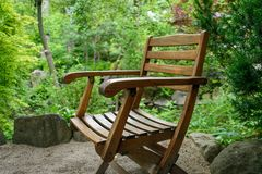 Closeup of an old wooden chair sitting in japanese zen garden stock image