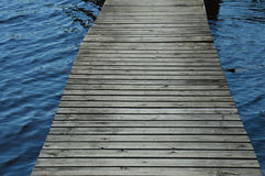 Weathered wood dock leading across the lake - passing stormy waters Royalty Free Stock Image