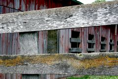 Weathered wood in layers. Weathered wood fence with lichens growing on; old barn in the background with faded paint Royalty Free Stock Photography