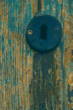 Weathered Wood with Metal Keyhole. Blue painted weathered door with old metal keyhole Royalty Free Stock Photo