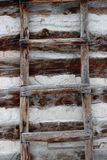 Rustic weathered primitive wood ladder. A weathered wood primitive ladder on a texture filled log cabin wall Royalty Free Stock Photo