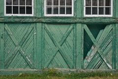 Weathered Wood Siding. Green wood siding of an old-looking, weathered building; white framed windows Stock Photos
