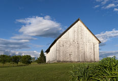 Weathered Wooden Barn. An old wooden barn weathered white in color on a green grassy hillside in New York's Hudson Valley Stock Image