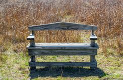 Weathered wooden bench in Texas prairie grass with morning sunlight. Solitary weathered wooden bench amid Texas prairie grass with springtime morning sunlight Stock Photography