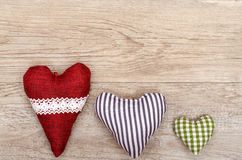 Wooden board with three hearts of cloth Royalty Free Stock Photos