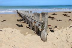 A weathered wooden breakwater on a sandy beach Royalty Free Stock Photo
