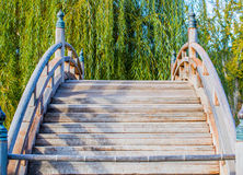 Weathered wooden curved bridge over a pond Stock Photo