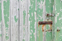 Weathered wooden door peeling green paint. With rusty bolt and lock Stock Image