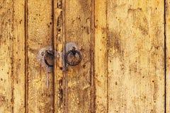 Weathered wooden door with rusty metal knockers Stock Photography