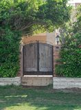 Weathered wooden garden gate surrounded by green climbing plants. At summer royalty free stock photo