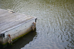 Weathered wooden jetty in calm water Stock Photo