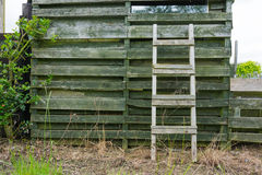 Weathered wooden ladder leaning on wooden slats Stock Image
