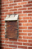Weathered wooden mail box. With red brick wall Stock Photography