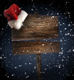 Weathered wooden sign with Santa hat in snow Royalty Free Stock Photography