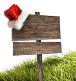 Weathered wooden sign with Santa hat on white. Weathered wooden sign with Santa hat and grass on white Stock Photo