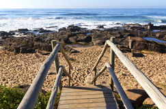 Weathered Wooden Stairway Leading onto Rocky Beach Stock Photos