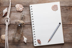 Weathered wooden table with blank notepad Royalty Free Stock Photos
