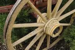 Weathered Wooden Wheel. Wagon wheel with spokes and weathered with age.  Paint is peeling and metal rusting Stock Photo