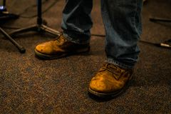 Weathered Work Boots Made of Leather. Weather used old work boots made of leather, either steel toed or not with denim jeans pants standing on a carpeted floor royalty free stock photo