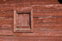 WEATHERED WORN RED BARN WOOD SIDING. The siding of a barn with a covered up window shows the weathered effects of years of rain , snow and wind royalty free stock photography