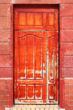 Weathered worn red door Stock Images
