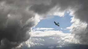 Weathering the storm. Biplane escaping stormy weather by flying into the opening in clouds Royalty Free Stock Photography