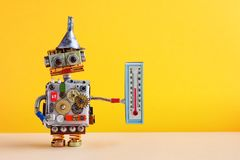 Weathermen robot with thermometer displaying comfort room temperature 21 degree celsius. Weather forecasting concept. Photo. Funny head robotic toy character on royalty free stock photos
