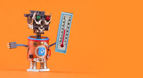 Weathermen robot with thermometer displaying comfort room temperature 21 degree celsius. Weather forecasting concept. Photo. Funny head robotic toy character on stock photos