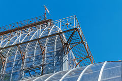 Weathervane auf dem Dach des Glasdachs des Gewächshauses gemacht vom Glas und vom Stahl Lizenzfreie Stockfotos