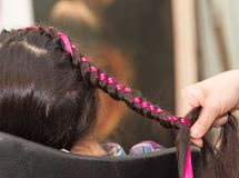 Weave braids in a beauty salon. Photo in the studio Royalty Free Stock Photo