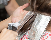 Weave hair in a beauty salon. The person is engaged in work Royalty Free Stock Photos