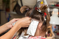 Weave hair in a beauty salon. The person is engaged in work Stock Photos