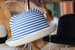 Weave hat on horizontal Stripes of blue and white color hanging on the hat hanger for sale. Clothing accessories and travel concept stock image