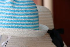 Weave hat on horizontal Stripes of light blue and white color hanging on the hat hanger for sale royalty free stock image