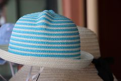 Weave hat on horizontal Stripes of light blue and white color hanging on the hat hanger for sale royalty free stock photography
