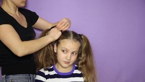 Weave a little cute girl pigtails. The Barber makes a girl hairstyle. stock video footage