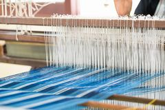 Weave silk cotton on the manual wood loom. In Thailand ,The process of silk weaving in the production of Thai silk stock photo